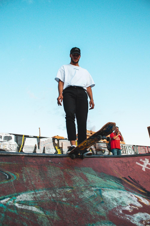 man wearing white shirt and black pants standing on skateboard ramp