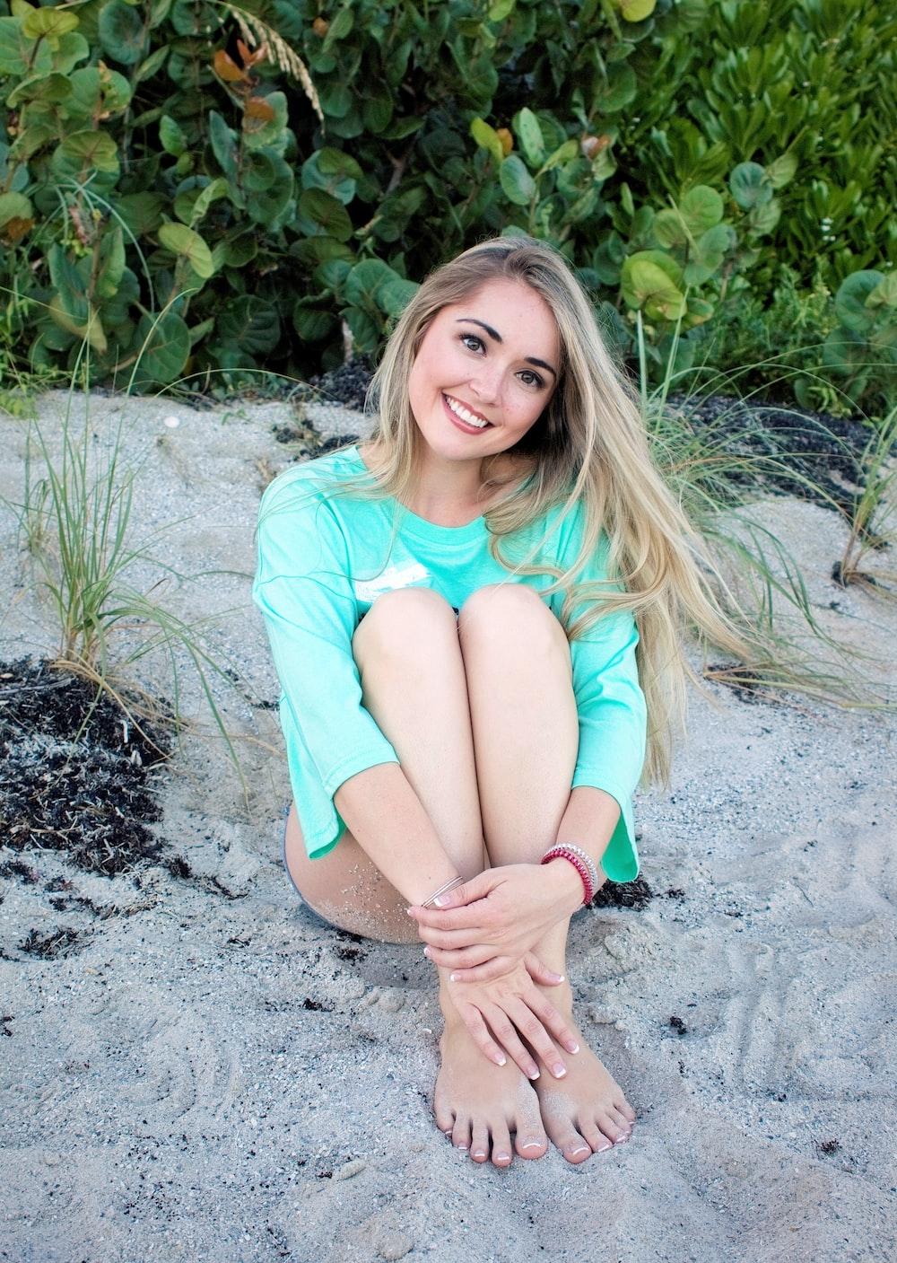 smiling girl sitting on sand during daytime