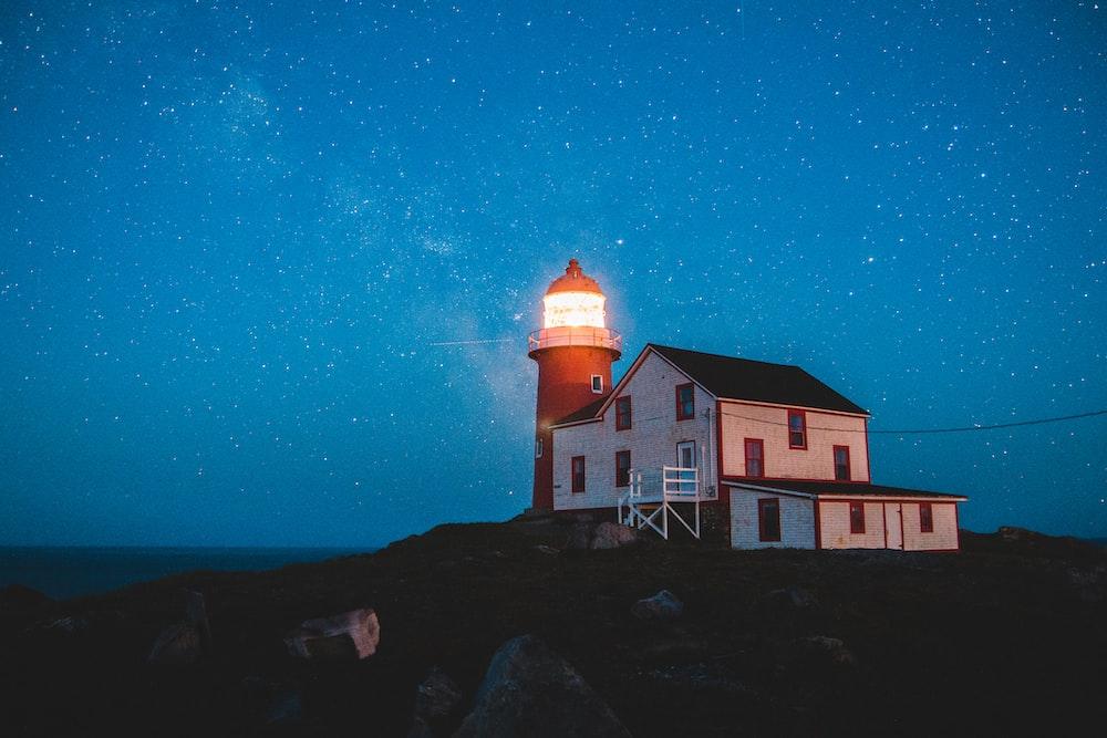 white wooden house beside lighthouse