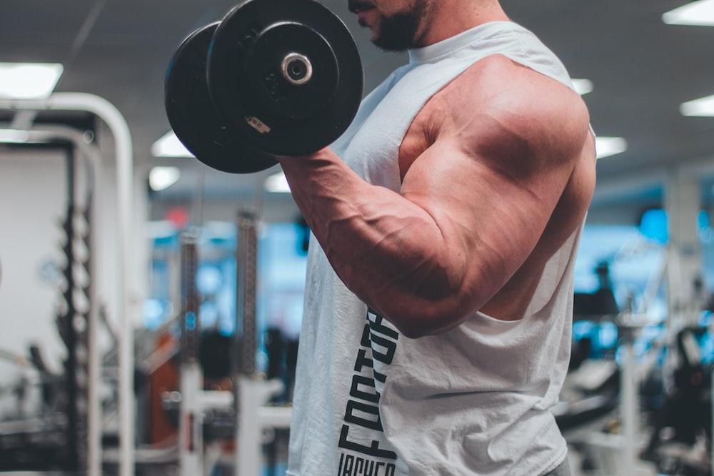 man in white tank top lifting black dumbbell
