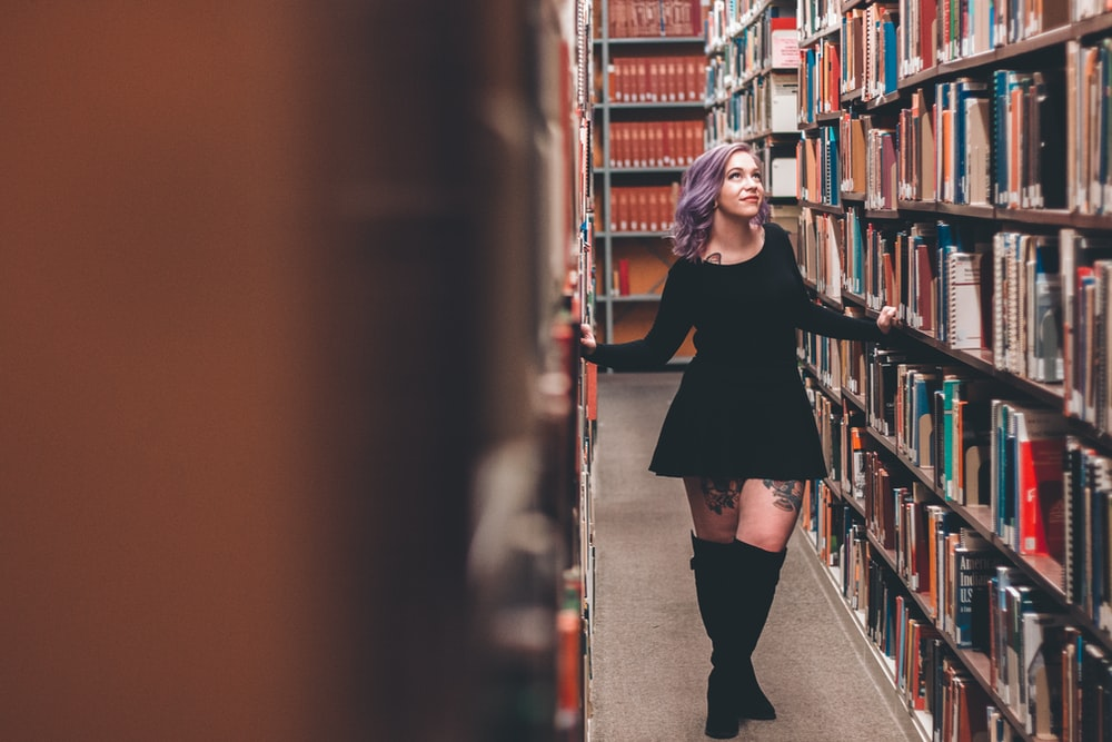 woman standing in middle of bookshelves