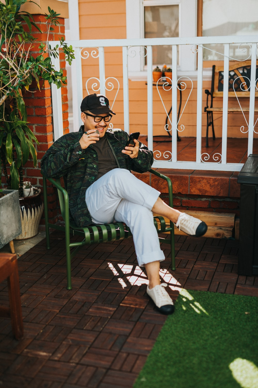 laughing man sitting on chair while using smartphone