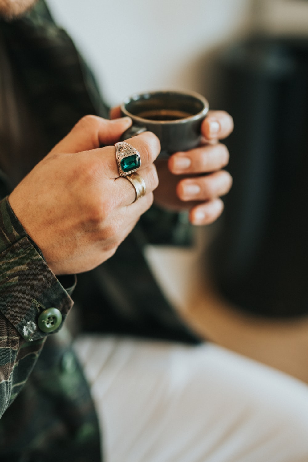person holding gray teacup