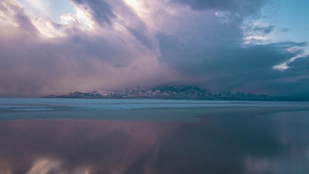 A Half Frozen Lake Next To A Mountain At Sunset.  - unsplash
