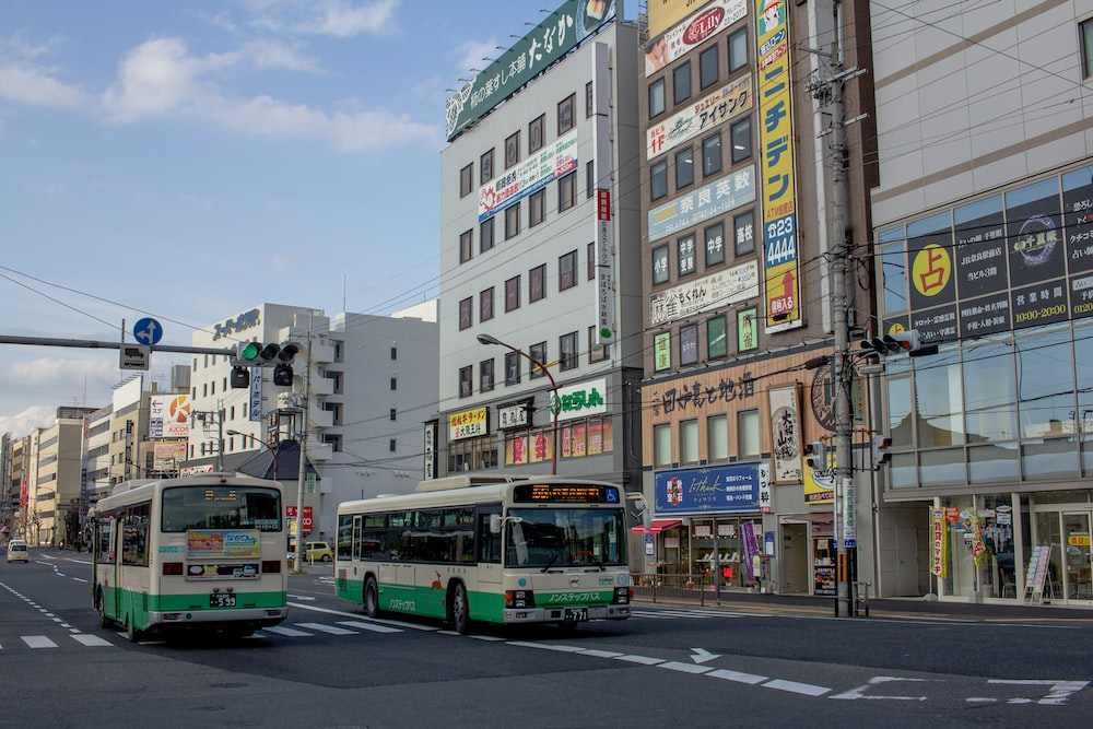 two white-and-green buses on road during daytime