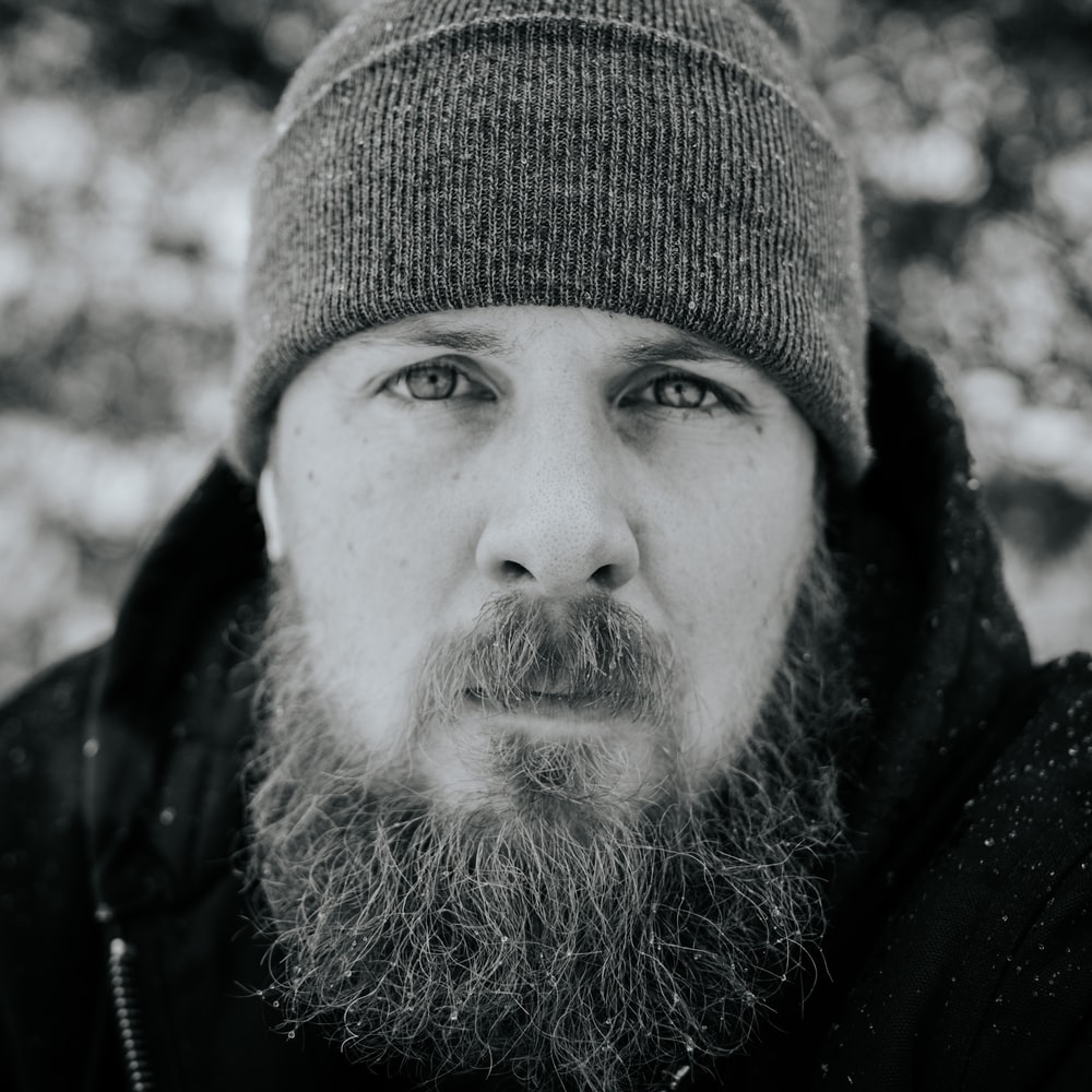 grayscale photography of man jacket and knit cap