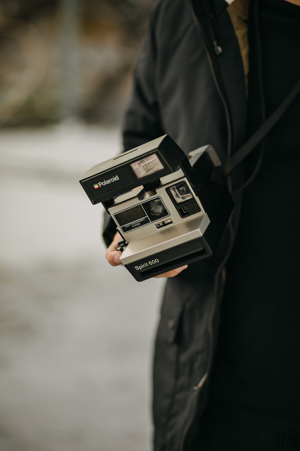 selective focus photography of person holding gray and black camera