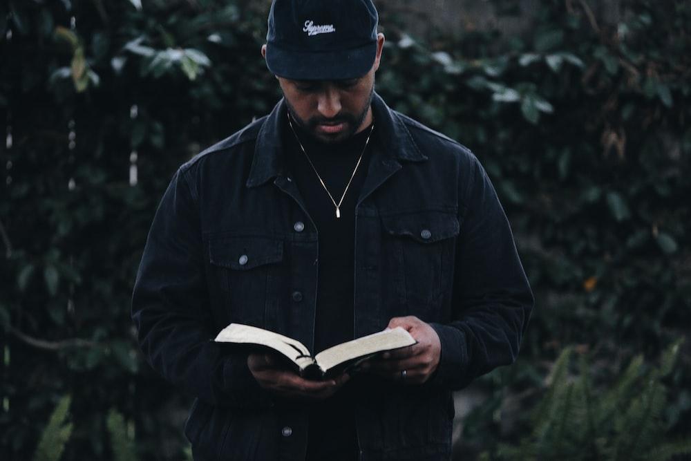 man in black jacket holding book