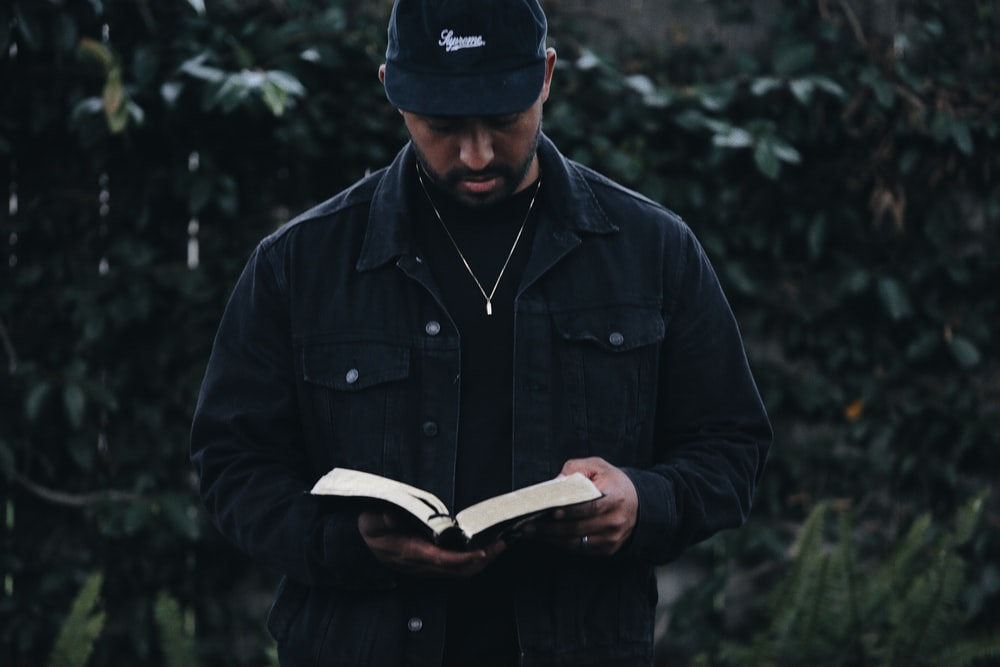 man in black jacket holding book
