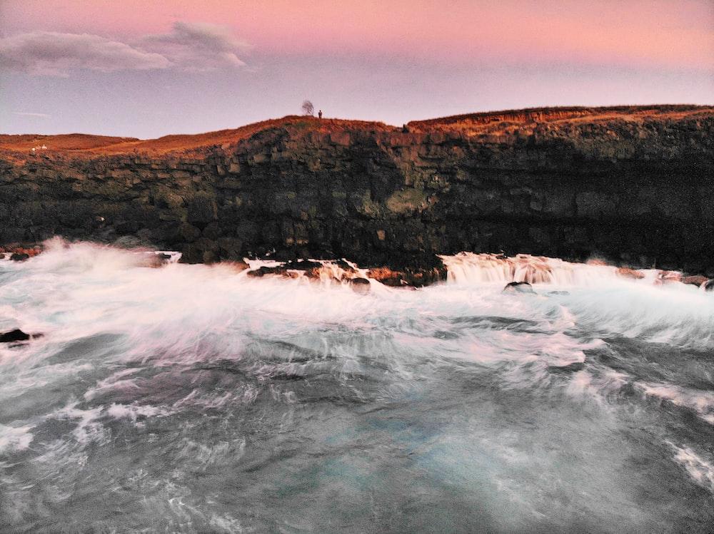 body of water beside cliff