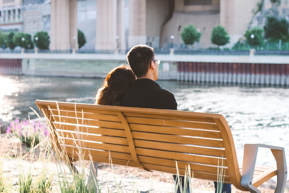 couple sitting on brown bench
