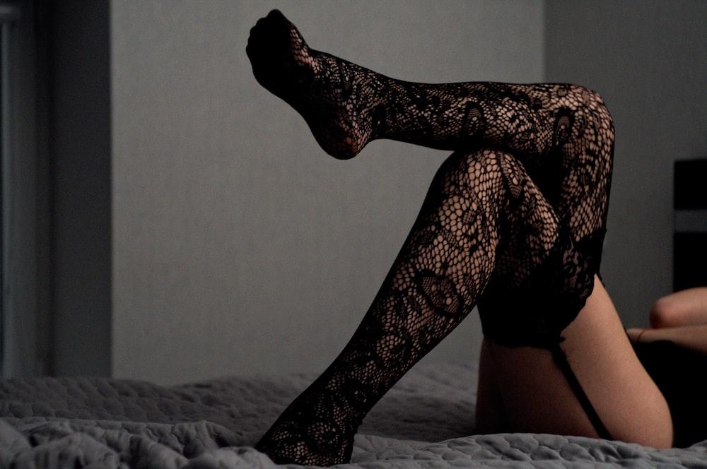 lying down person wearing black thigh-high socks
