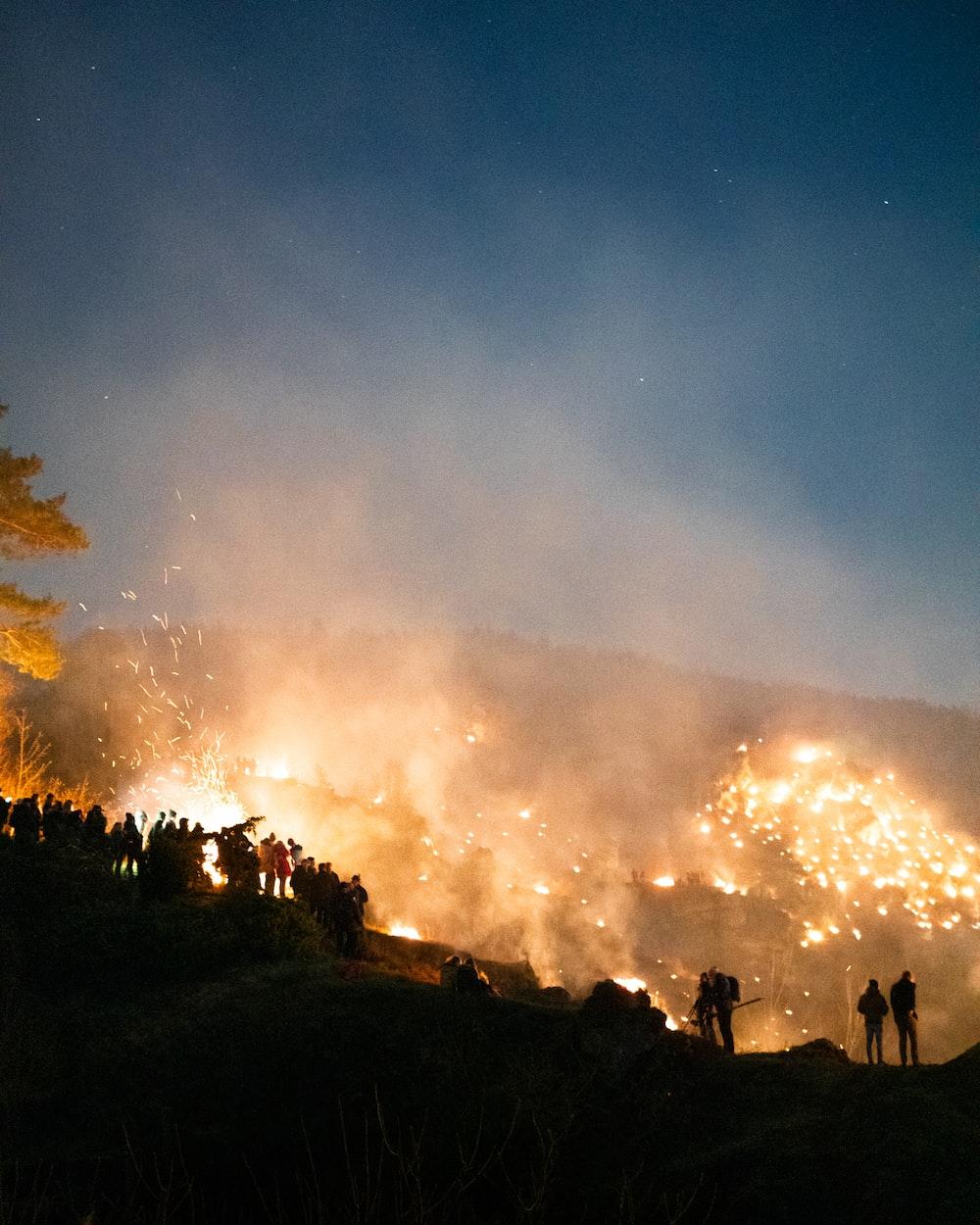 people standing on mountain near bush fire