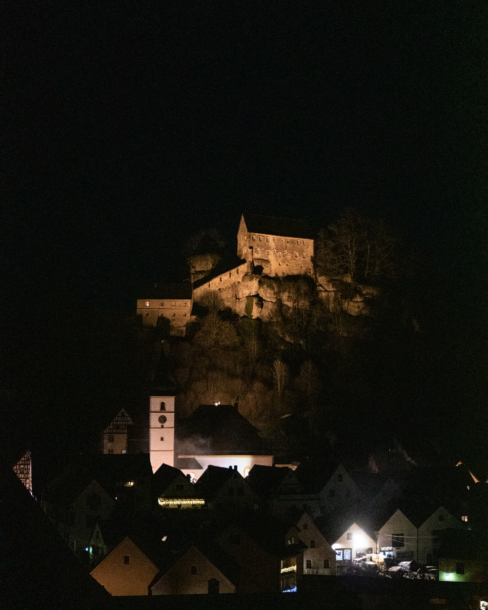 castle surrounded with houses view at night