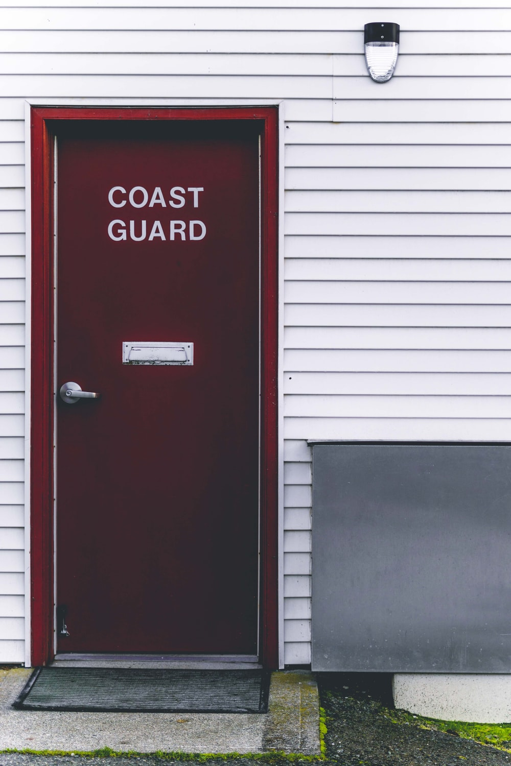 closed red and white Coast Guard wooden door
