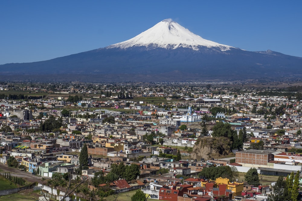 cityscape and volcano under blue sky