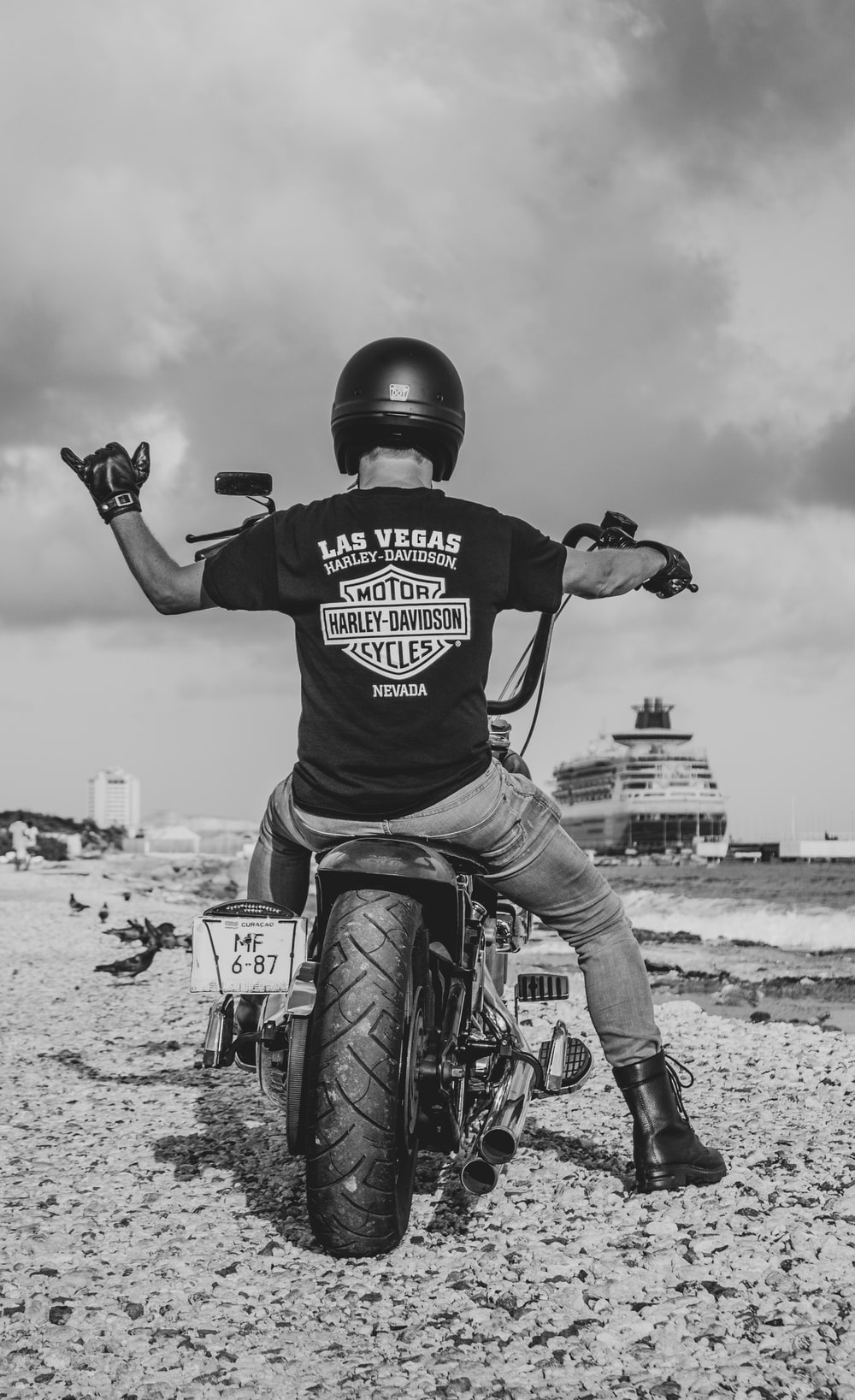 grasyscale photo of man in Harley-Davidson t-shirt riding cruiser motorcycle on shore