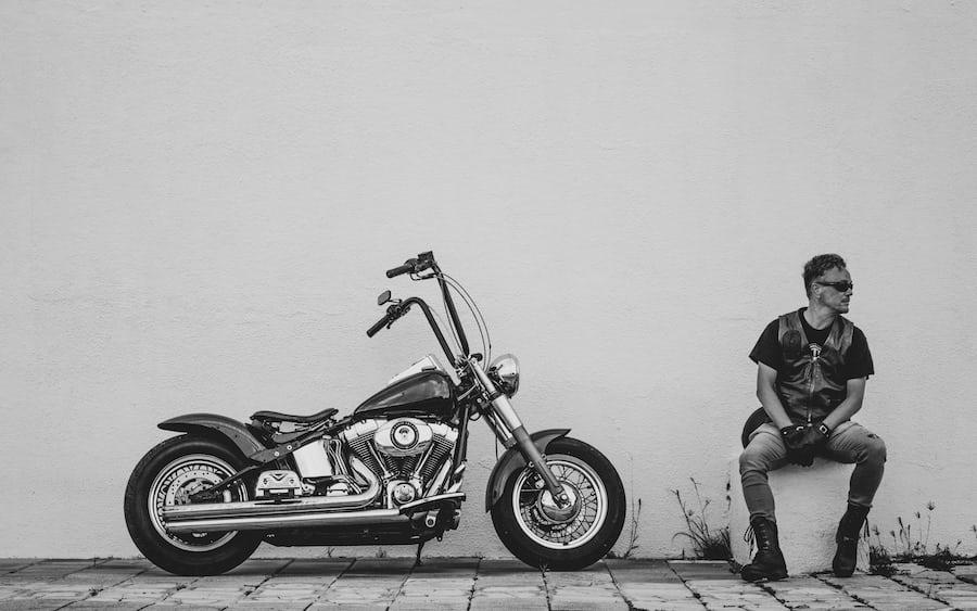 man sitting next to harley davidson dyna motorcycle
