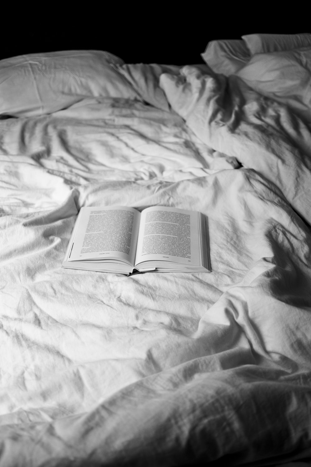 opened white book on bed