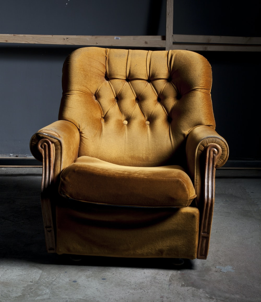 shallow focus photo of brown padded armchair