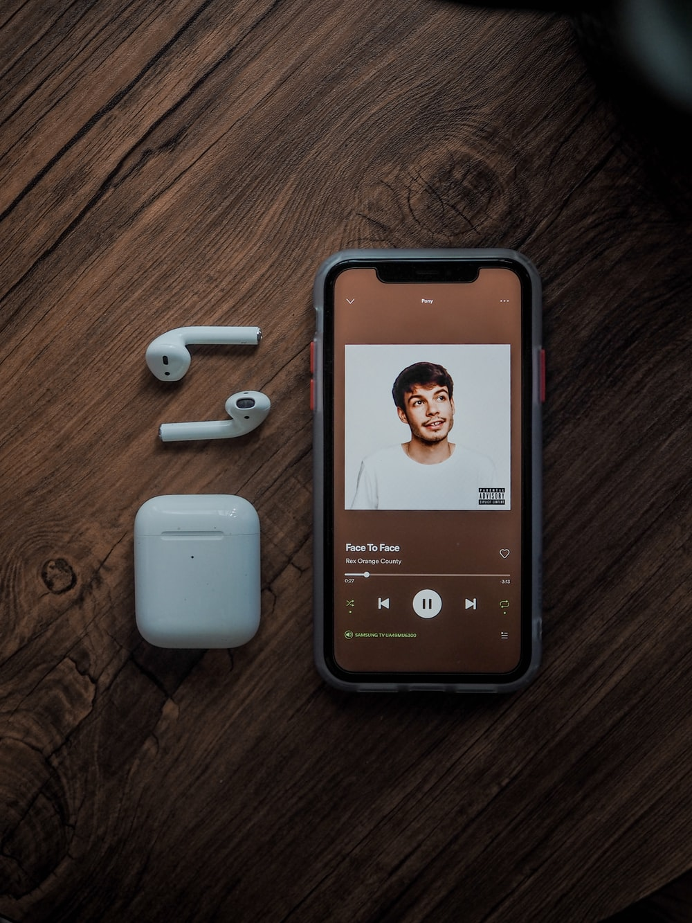 turned on smartphone beside Apple AirPods and case