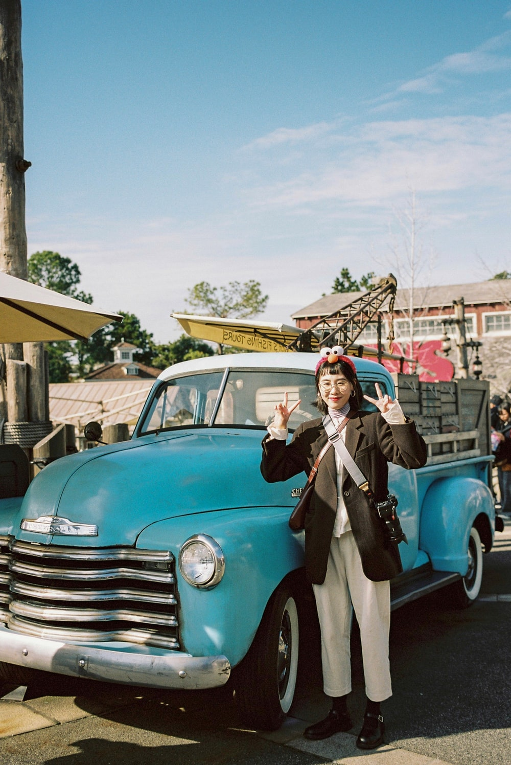 woman standing beside classic blue pickup truck
