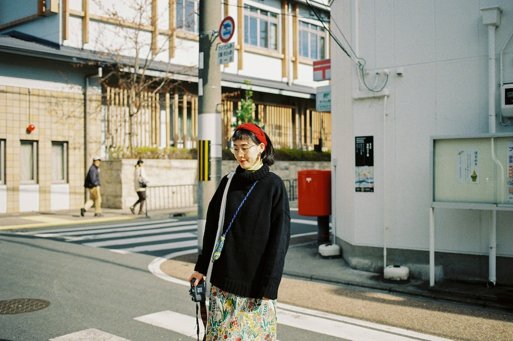 woman standing near white building