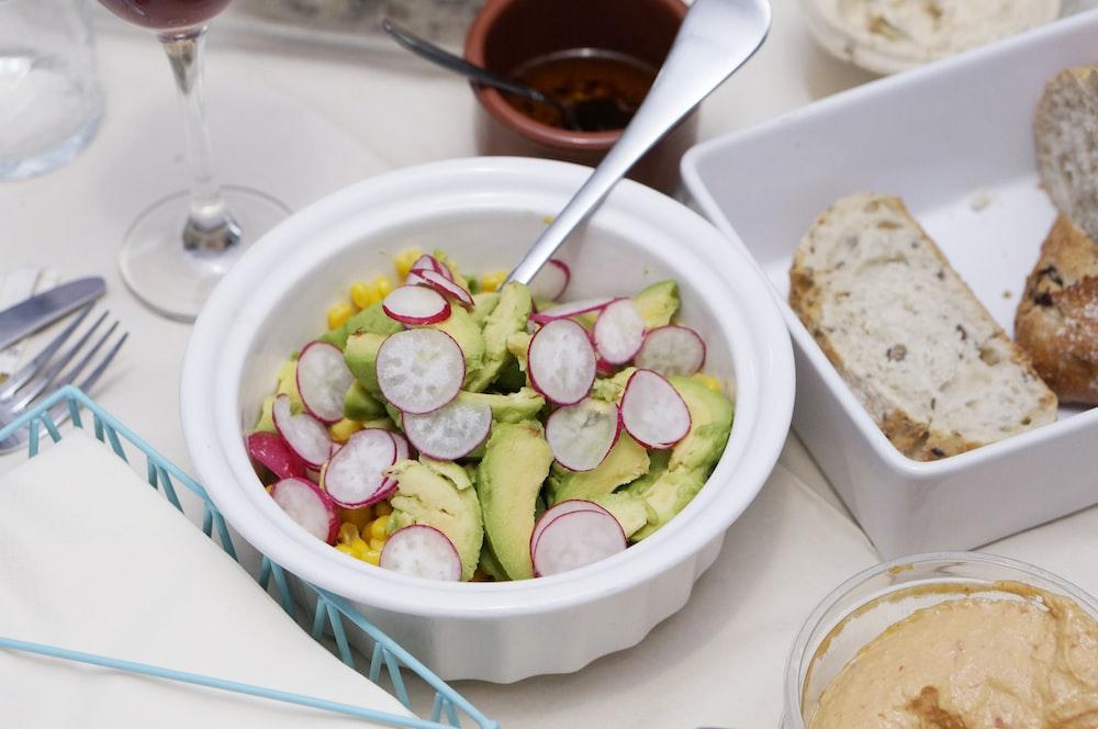 sliced vegetables in bowl beside breads