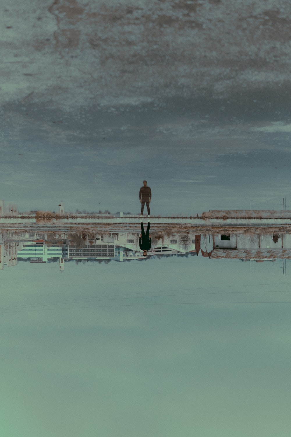 person in black long-sleeved shirt standing in front of body of water under cloudy sky