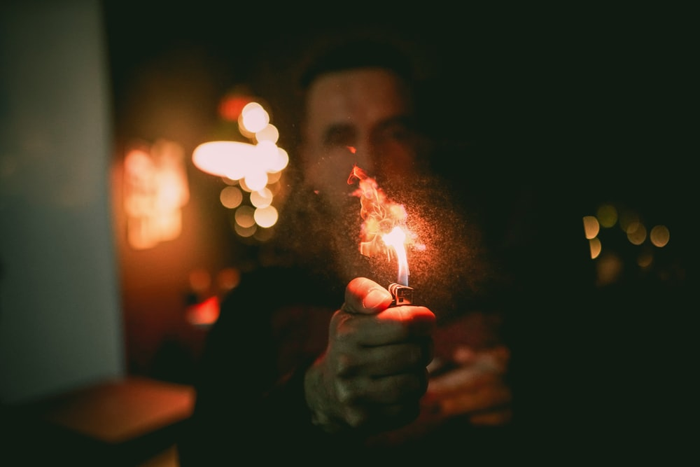 shallow focus photo of person using lighter