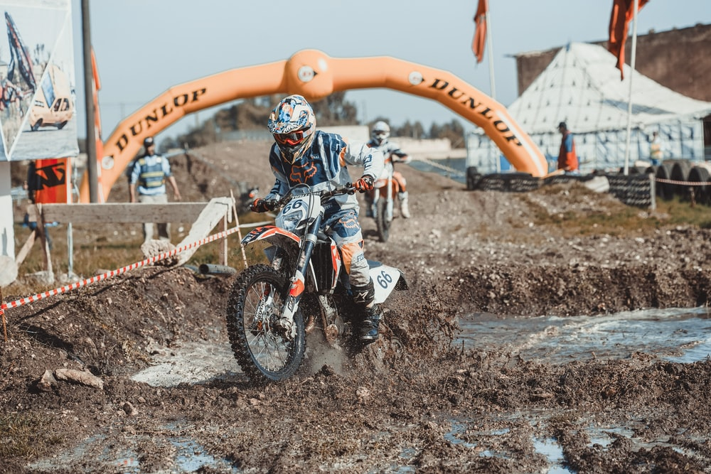 time-lapse photography of man riding a motocross in a muddy road