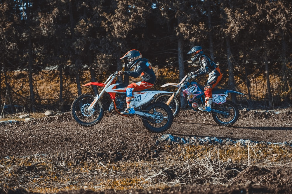shallow focus photo of person riding motocross dirt bike during daytime