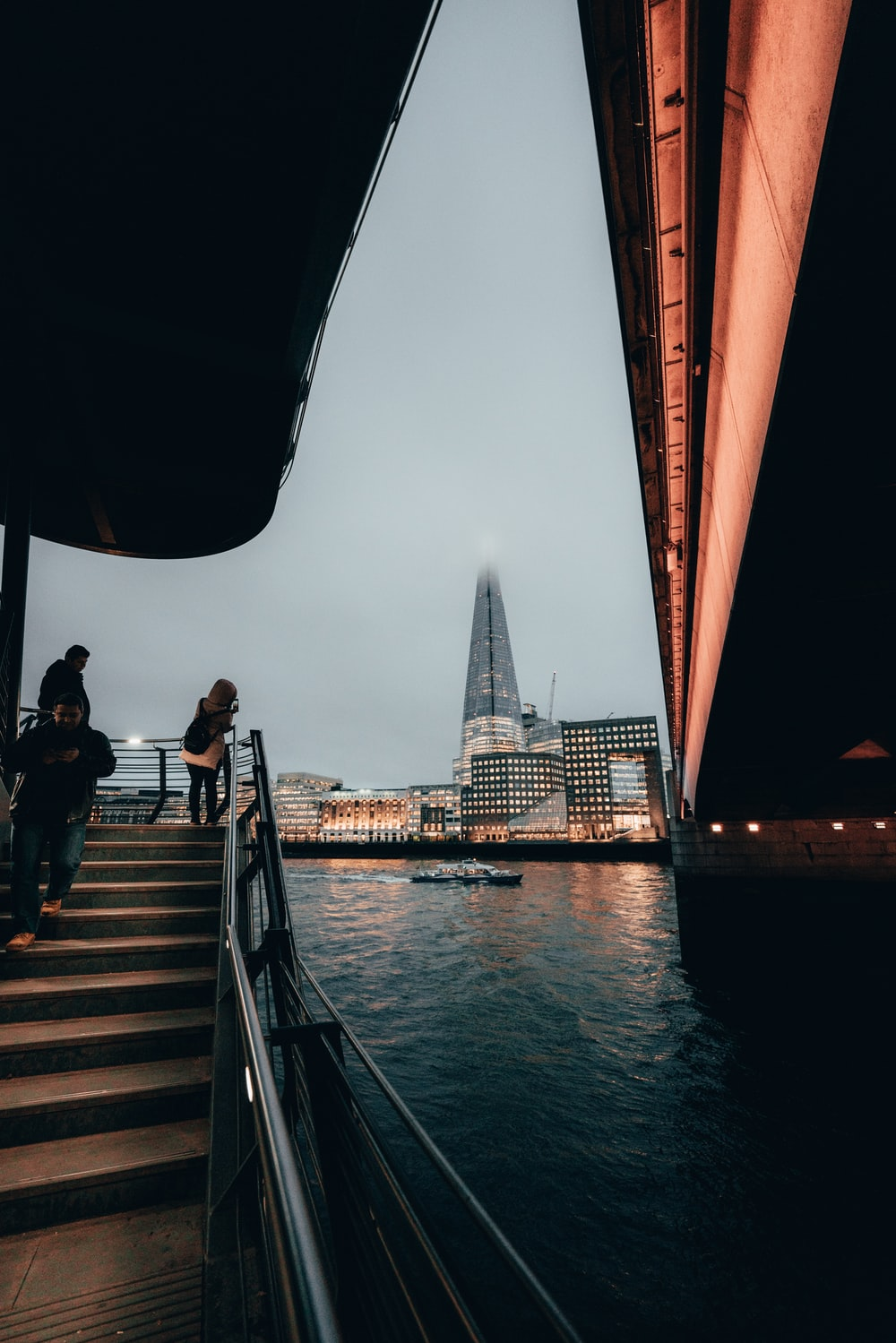 people standing on boat under bridge