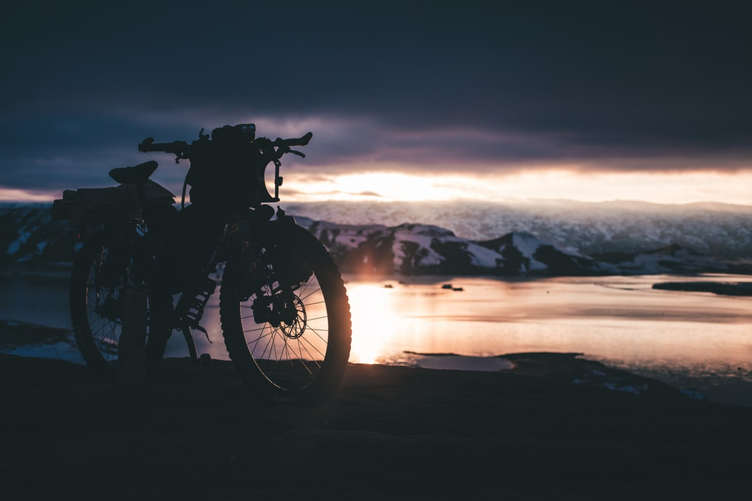 Motorcycle Park Near Body of Water Under Dark Clouds - unsplash