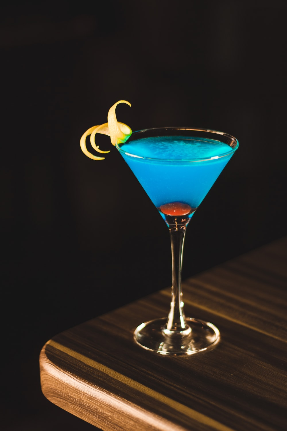 blue drink in wine glass on corner of wooden table