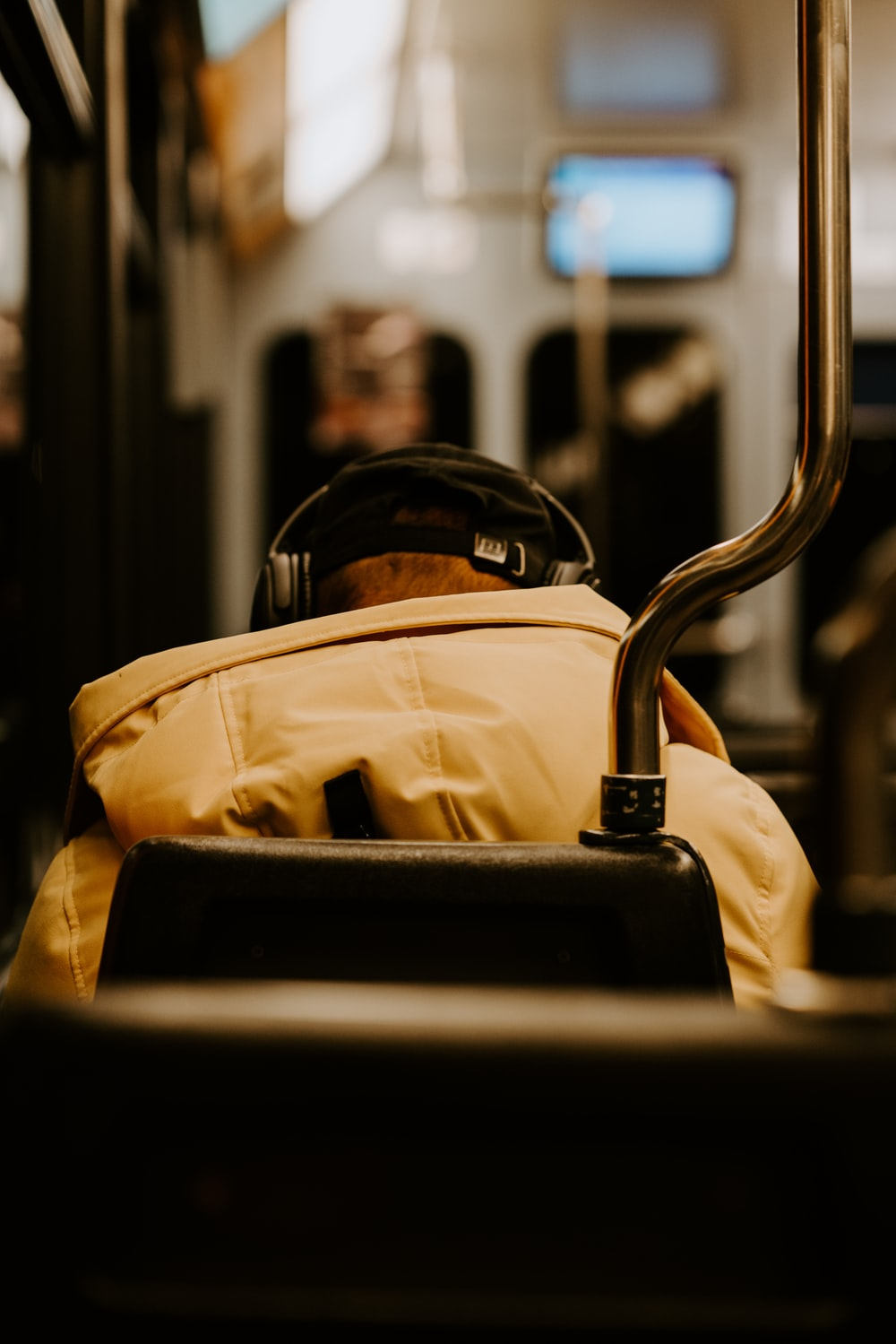 person wearing brown hooded jacket using black headphones while sitting on gray chair