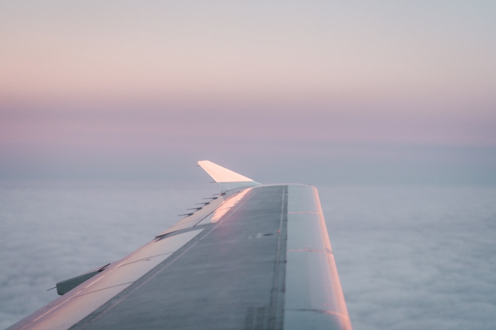 airplane in mid air above clouds during day