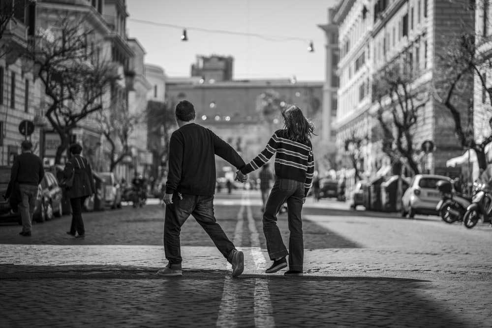 man and woman holding hands and crossing the road near people and vehicles during day