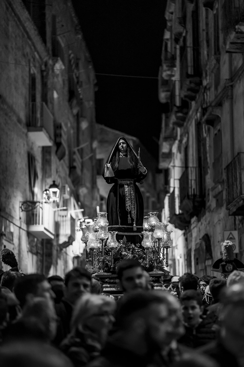 grayscale photography of group of people carrying religious statuette