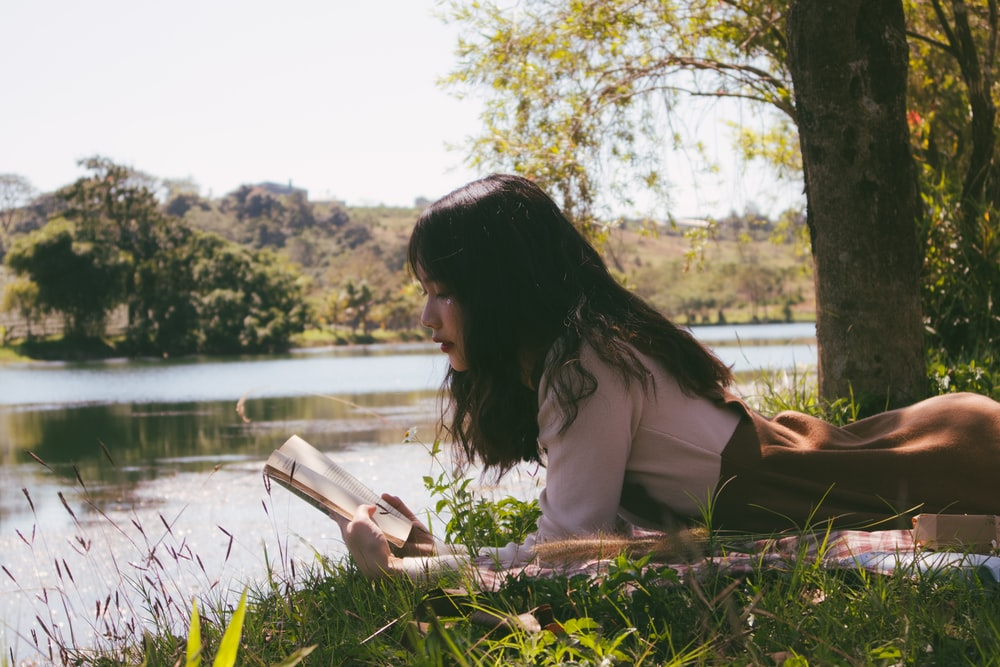 woman reading book and lying forward on sheet on grass beside body of water during day