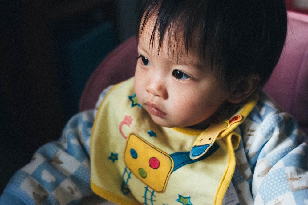 baby wearing yellow bib