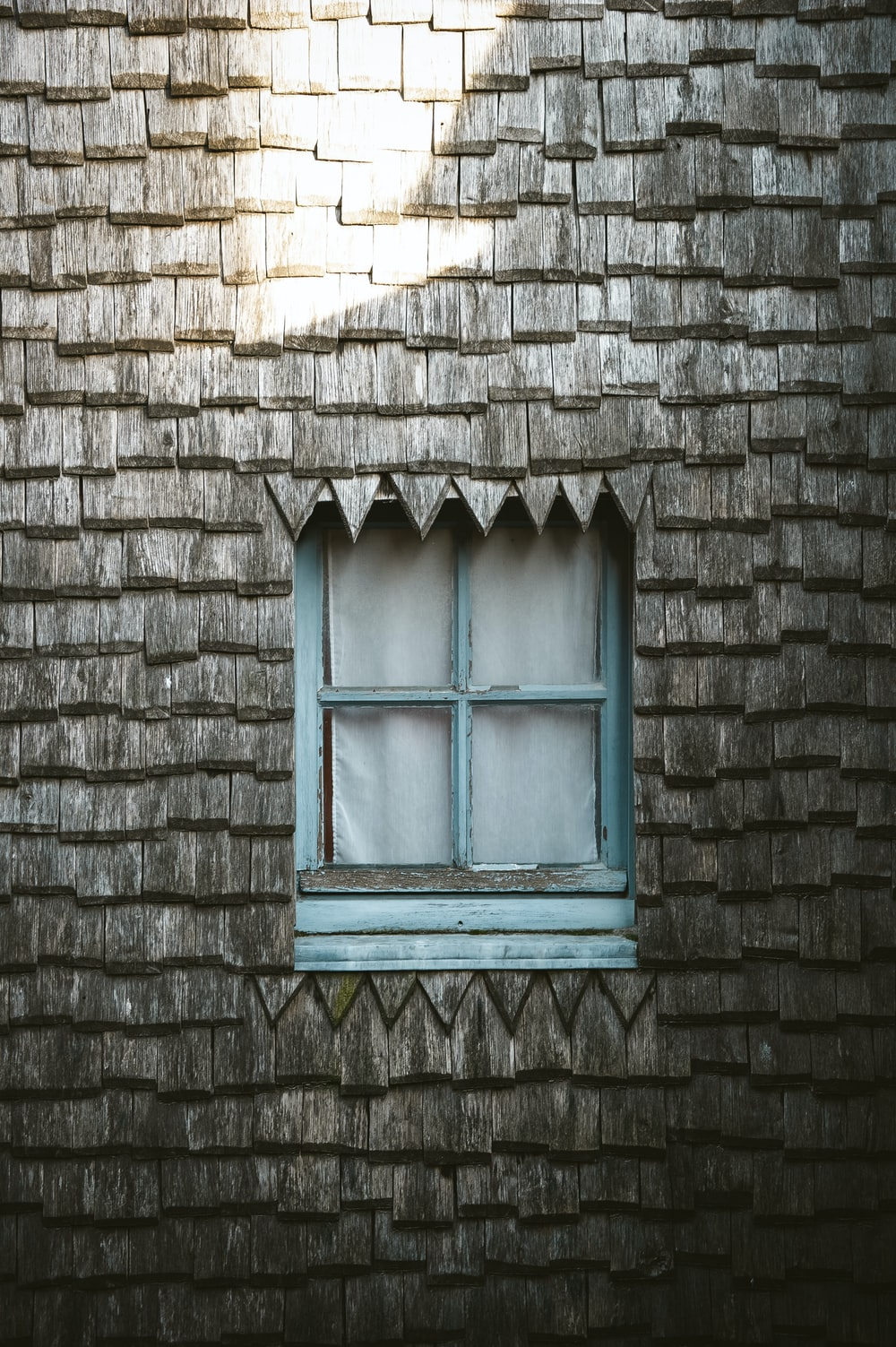 gray wooden house with closed blue wooden framed glass window