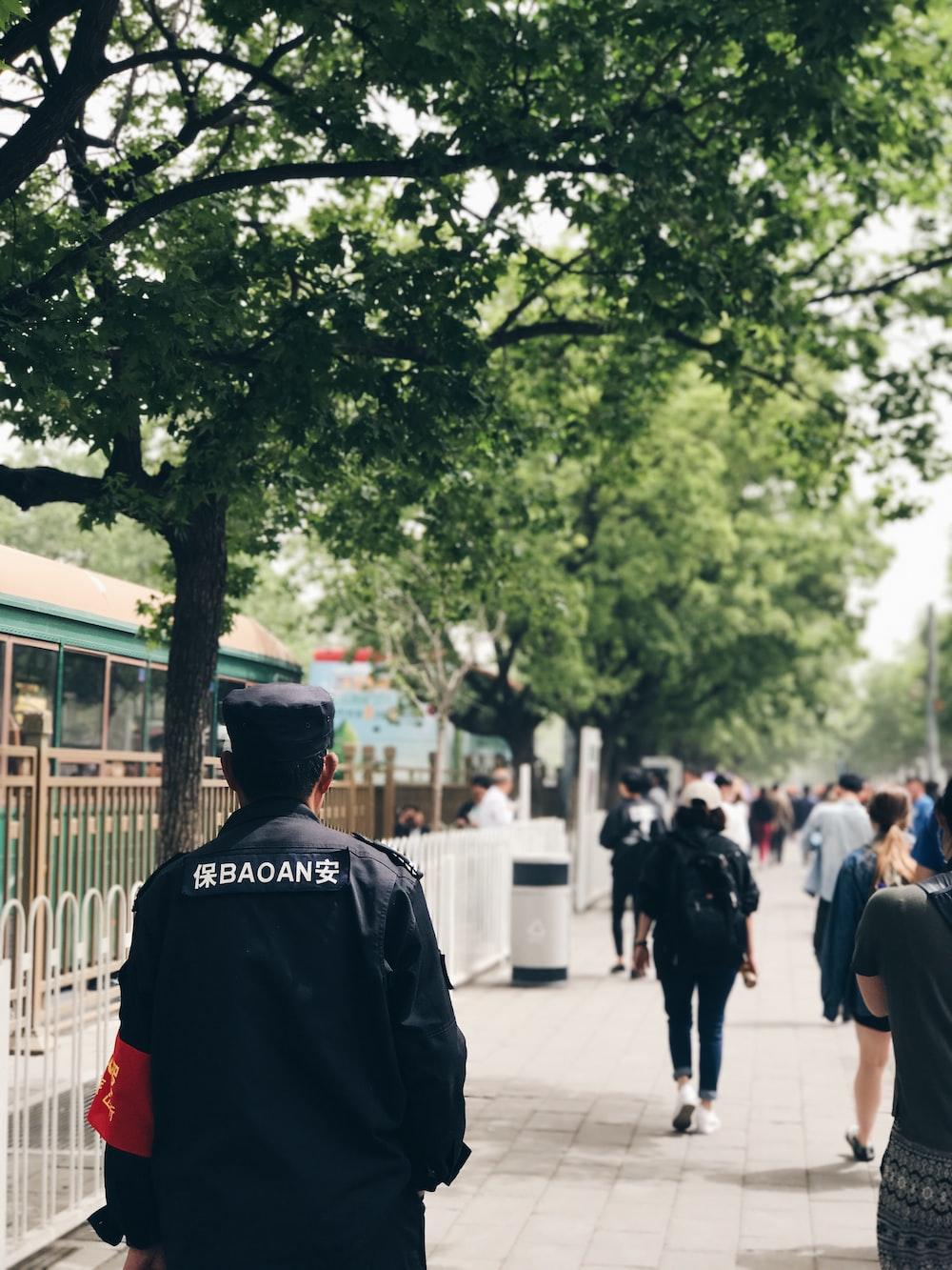 people walking on sidewalk near fence and trees