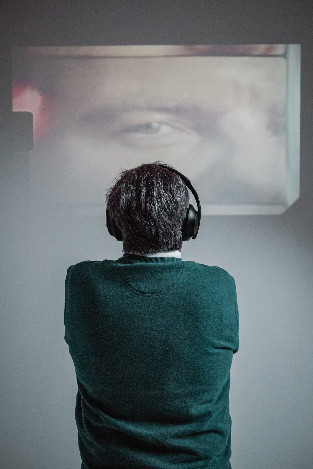 person wearing green shirt using black headphones while standing and facing back and watching movie