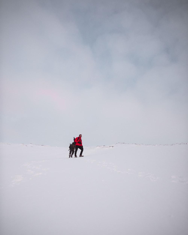 two men on snow field under cloudy sky