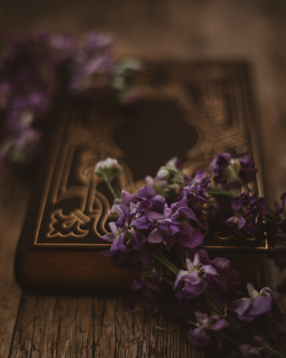 selective focus photography of purple flowers on closed book