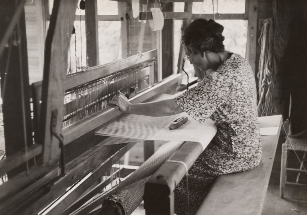 sitting woman using weaving machine