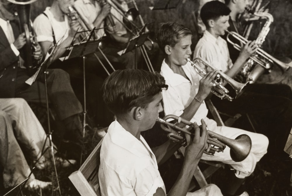 grayscale photography of group of people playing instruments