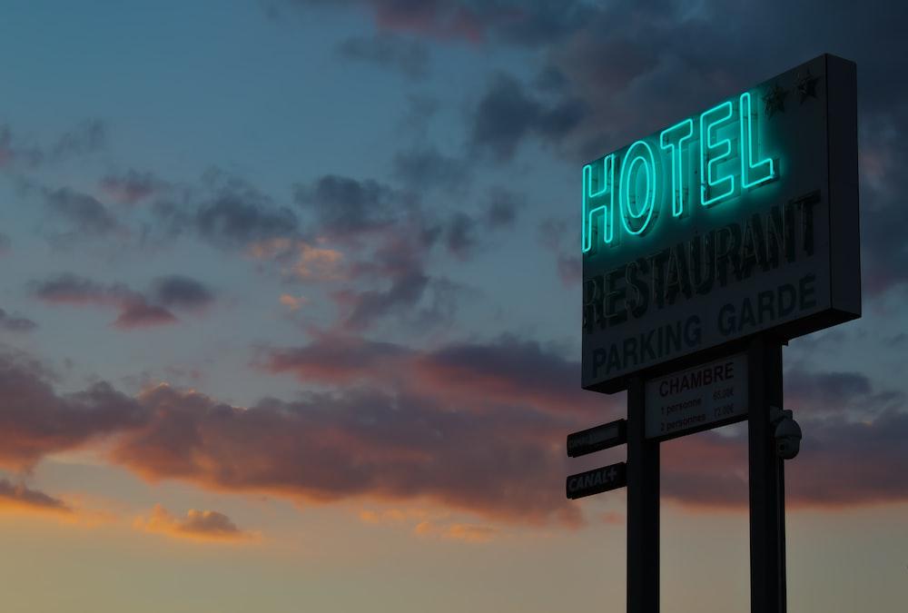 turned-on green hotel LED light signage ahead