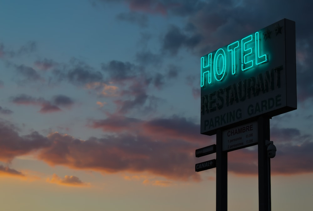 turned-on green hotel LED light signage ahead